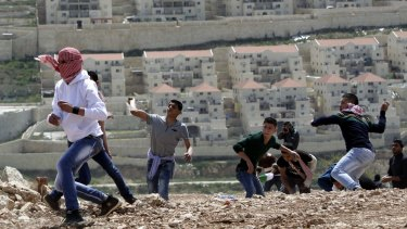 Palestinian youths throw stones at Israeli soldiers near the settlement of Beitar Illit in March, during protests to mark Land Day.