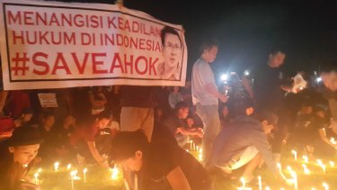 "Supporters conduct a candlelit vigil in Bali in support of Ahok. The sign reads ""Bitter over the lack of justice in Indonesian law""."