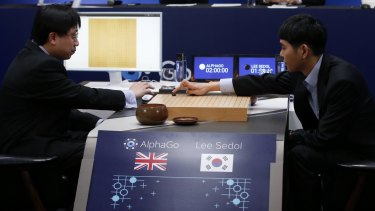 South Korean professional Go player Lee Se-dol, right, puts the first stone against Google's artificial intelligence program, AlphaGo, with Google DeepMind's lead programmer Aja Huang, left.