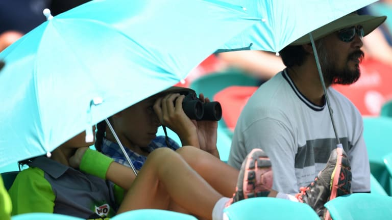 Taking cover: Spectators shelter from the sun and heat at the SCG.