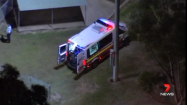 An ambulance waits in Glenmore Park where a woman was stabbed multiple times.
