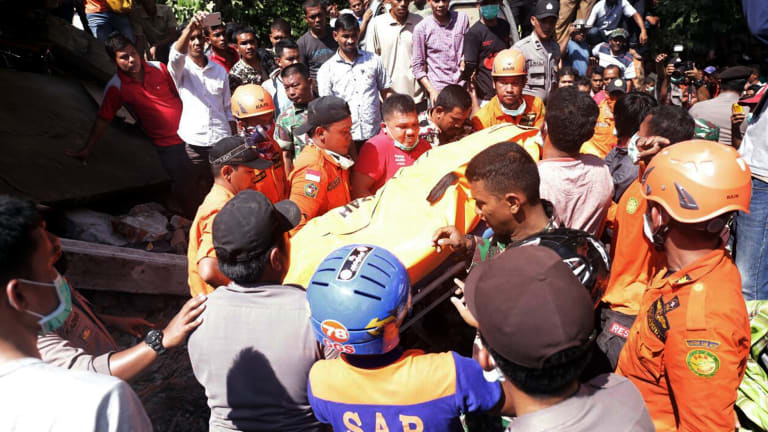 Rescuers carry a body bag containing a victim recovered from a building that collapsed after the earthquake.