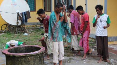Migrants brush their teeth and clean up at the temporary shelter in Lhoksukon.