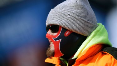 A fan is bundled against the cold weather as he watches teams warm up before an NFL football game in Massachussets.
