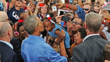 President Barack Obama kisses a young child during a campaign event in Kissimmee, Florida.