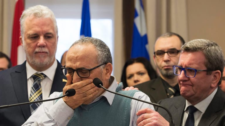 Mohamed Labibi, president of the Islamic cultural centre, is comforted by Quebec Premier Philippe Couillard, left, and Quebec City mayor Regis Labeaume, right, during a news conference.
