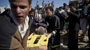 Yemenis carry the body of a child from houses hit by Saudi air strikes near Sanaa Airport on March 26.