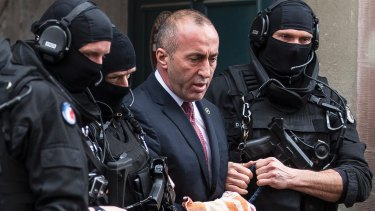 Former prime minister of Kosovo Ramush Haradinaj  leaves the court escorted by hooded police officers in Colmar, eastern France on  January 12.