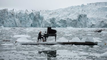 Italian composer and pianist Ludovico Einaudi performs one of his own compositions on a floating platform in the Arctic Ocean, in front of the Wahlenbergbreen glacier, in Svalbard, Norway, to highlight the impact of climate change.