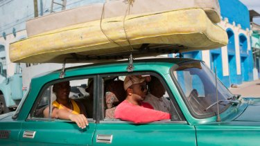 People carry their mattresses on a car toward a shelter prior the arrival of the Hurricane Matthew in Santiago, Cuba.