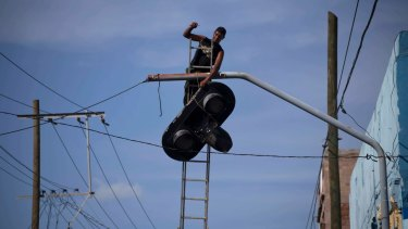 A worker dismantles a traffic light before the arrival of Hurricane Matthew in Santiago, Cuba.