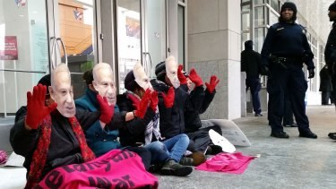 """Demonstrators wear masks bearing the likeness of Israeli Prime Minister Benjamin Netanyahu and hold up """"bloody"""" hands  outside the Washington Convention Center, which is hosting the American Israel Public Affairs Committee (AIPAC) annual policy conference."""
