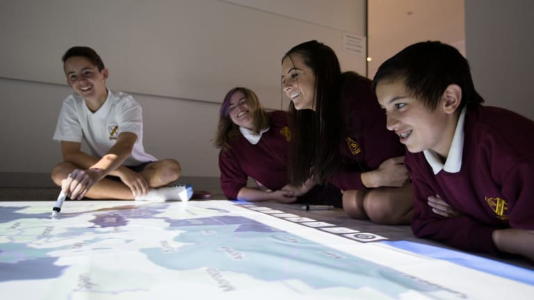 Students from Campbelltown Performing Arts School, (L-R) Levi Crossman, Bethany Lewis, Bronte Galla-Laine, and Blake Fernandez, use the giant floor whiteboard at a media event to promote the classroom of the future at the Education Department in Eveleigh.