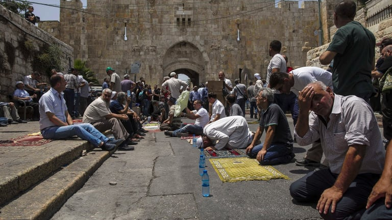 Palestinians pray outside the Lions' Gate in Jerusalem's occupied Old City on Friday.
