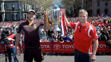 Hawthorn's Luke Hodge and Sydney's Kieren Jack hold up the AFL Premiership Cup during the 2014 parade.