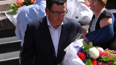 Premier Daniel Andrews lays flowers in the Bourke Street Mall on Saturday morning.