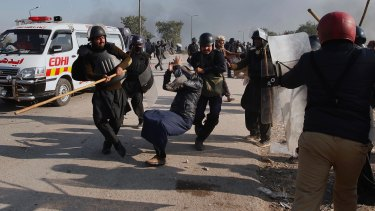 Police officers beat a protester during a clash with protesters in Islamabad.