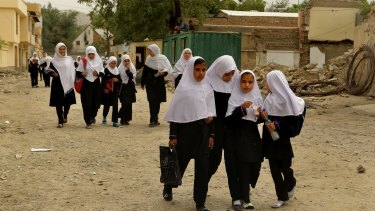 Schoolgirls walk home after class through the streets of Kabul.
