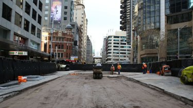 Workers prepare the road surface on Sunday for resealing at the busy intersection on George Street.