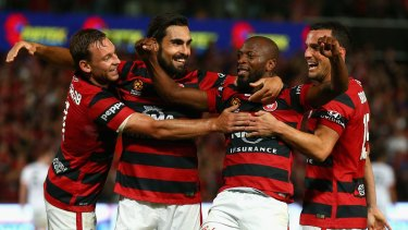 Remarkable win: Romeo Castelen celebrates scoring a goal with teammates against the Brisbane Roar at Pirtek Stadium.