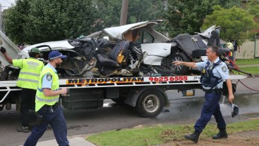 The wreckage of the car is towed away.