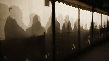 Migrants are silhouetted as they warm themselves inside a waiting tent to get an appointment at the central registration center for refugees and asylum seekers in Berlin on Wednesday.