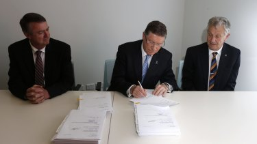 Denis Napthine, centre, signs the EWL contract with Terry Mulder and Ken Mathers.