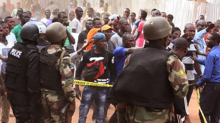 Mali troops try to control a crowd of onlookers near the Radisson Blu hotel, after Islamic extremists armed with guns and grenades stormed it on Friday morning.