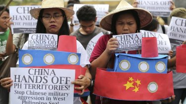 Filipino student activists hold mock Chinese ships to protest China's recent island-building and alleged militarisation of the disputed Spratly Islands.