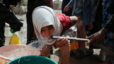 Cholera is usually spread in water: a girl drinks water from a well on the outskirts of Sanaa, in Yemen.