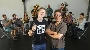Beatboxer Chris Gale and director Felix Cross stand in front of Symphony Under the Star's brass ensemble.