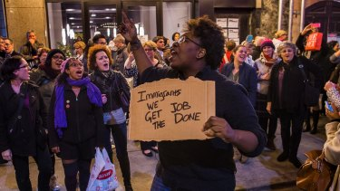 Protesters shout slogans at Vice President-elect Mike Pence as he leaves the Richard Rodgers Theatre after a performance of <i>Hamilton</i>. The slogan on the placard refers to a song in the show.