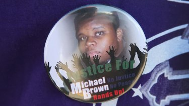 A resident wears a button featuring a picture of teenager Michael Brown, who was killed by police officer Darren Wilson on August 9.