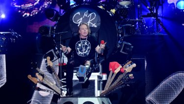 Nursing a broken foot, Axl Rose of Guns N' Roses performs on a throne at Coachella on Saturday. His promotion to the job of lead singer for AC/DC has angered fans.