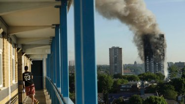 A resident in a nearby building watches smoke rise from the tower on fire in London.