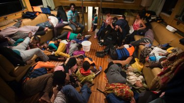 Refugees from Eritrea rest inside the Astral vessel after being rescued from the Mediterranean sea.