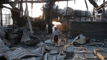 A man walks through the remains of a factory that was bombed twice in September outside Yemen's capital, Sanaa.