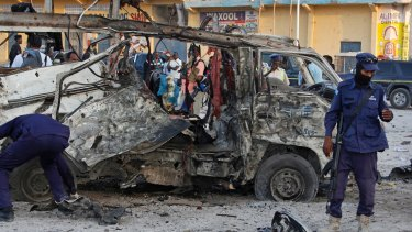 Security forces stand near the wreckage of a minibus at the scene of a car bomb attack in Mogadishu, Somalia on Thursday.