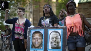 Demonstrators holding pictures of Timothy Russell and Malissa Williams protest the acquittal of Michael Brelo.