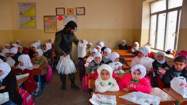 An Islamic State militant distributes bags full of stationery to Iraqi school pupils in Mosul, northern Iraq.
