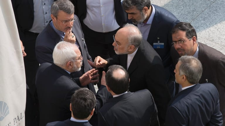 Mohammad Javad Zarif (centre, left) and the head of Iran's atomic energy program Ali Akbar Salehi (centre, right) talk while aides listen after a negotiation session with John Kerry in Lausanne in March this year.