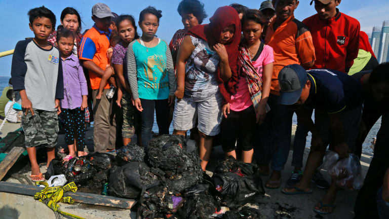 People at Muara Angke Port in Jakarta, Indonesia, inspect charred personal belongings of passengers on a ferry that caught fire.