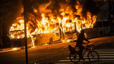 A man rides a bicycle past buses set on fire during a trade union general strike in Rio on Friday.