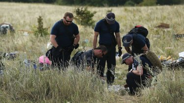 Australian Federal Police officers and their Dutch counterparts collect human remains from the MH17 crash site in the fields outside the village of Grabovka.
