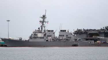 The damaged port aft hull of USS John S. McCain, left, is seen while docked next to USS America at Singapore's Changi naval base.