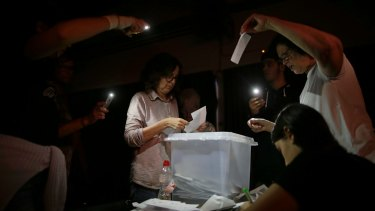 Volunteers start to count ballots during a blackout after the polling station closed at the La Llacuna school in Barcelona.