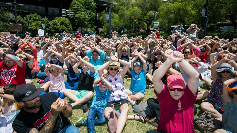 Protesters at First Fleet Park in Sydney clasp arms in the air to demonstrate solidarity with the men on Manus inj November.
