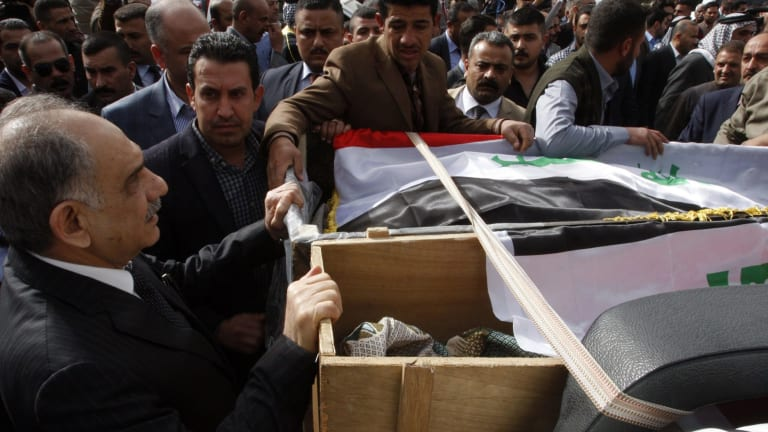 Iraqi Deputy Prime Minister Saleh al-Mutlaq (left) holds on to the coffins during the funeral of Sheikh Qasim al-Janabi and his son, Mohammad.
