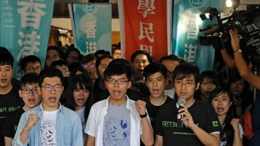 Hong Kong activists, from left to right front row, Nathan Law, Joshua Wong and Alex Chow chant slogans outside the high court in Hong Kong on Thursday.