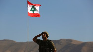 A Lebanese soldier salutes the national flag atop an armoured personnel carrier on the outskirts of Ras Baalbek, north-east Lebanon on Monday.